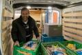voedselbank pakketten in busje laden vrijwilliger